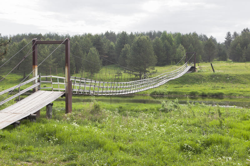 View of the suspension bridge over the river Vaga in village Lipki. Verkhovazhsky District, Vologda Region, Russia royalty free stock images
