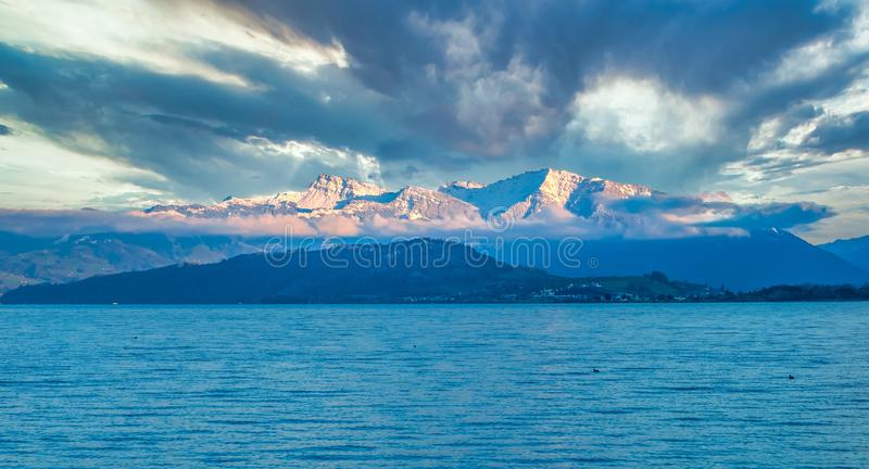 View of the Swiss Alps from the shores of the Upper Zurich Lake Obersee on a cloudy day, Hurden, Schwyz, Switzerland royalty free stock images