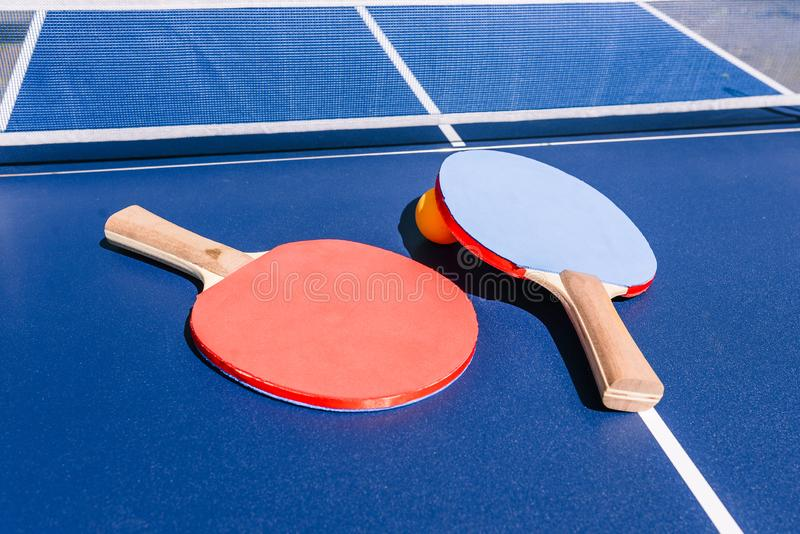 View of the table for playing table tennis. Two rackets and an orange ball. Sports equipment on the street. The concept of sports. Active recreation stock images