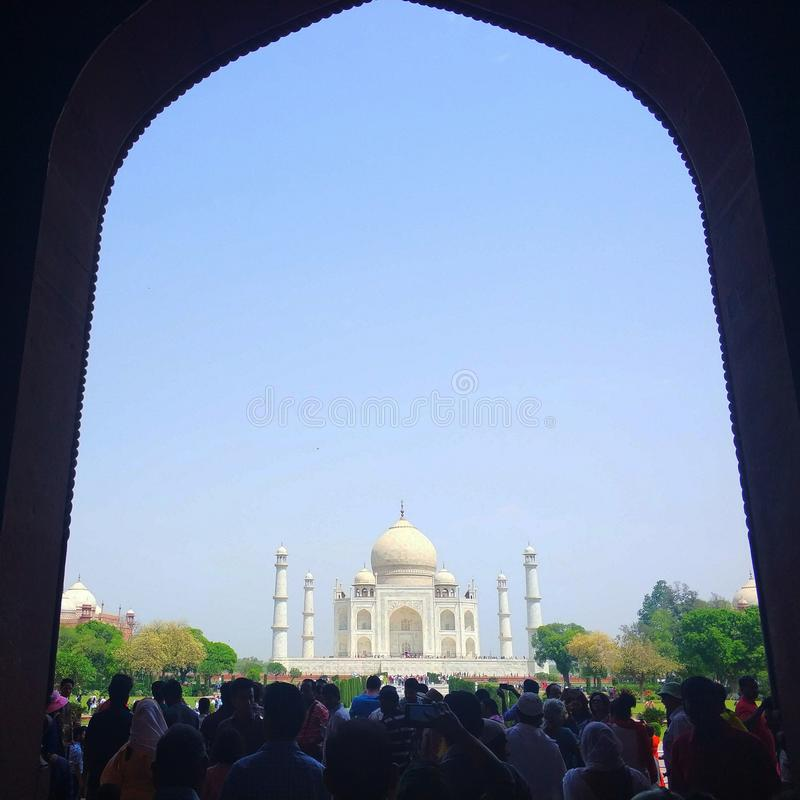 Taj Mahal view from the main entrance. A view of Taj Mahal the main entrance shadow as framing while tourist flocking the place royalty free stock photo