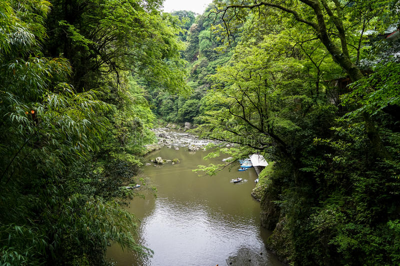View of Takachiho gorge from above seeing river, boats at pier a. Nd rocky shore through lush green trees and mountain background, Takachiho, Miyazaki, Japan stock images