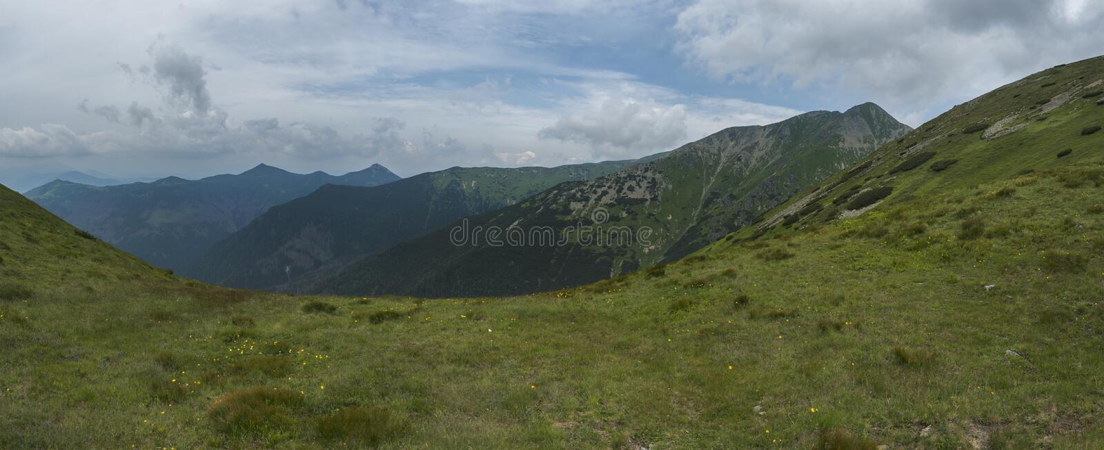 View from tatra mountain trail on Baranec to Western Tatra mountains or Rohace panorama. Grassy meadow hills, blue sky royalty free stock image
