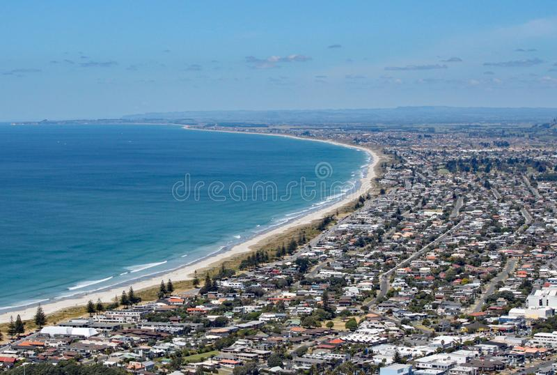 View of Tauranga from Mount Maunganui in New Zealand. The surf rolls on to the perfect sandy beach royalty free stock photos