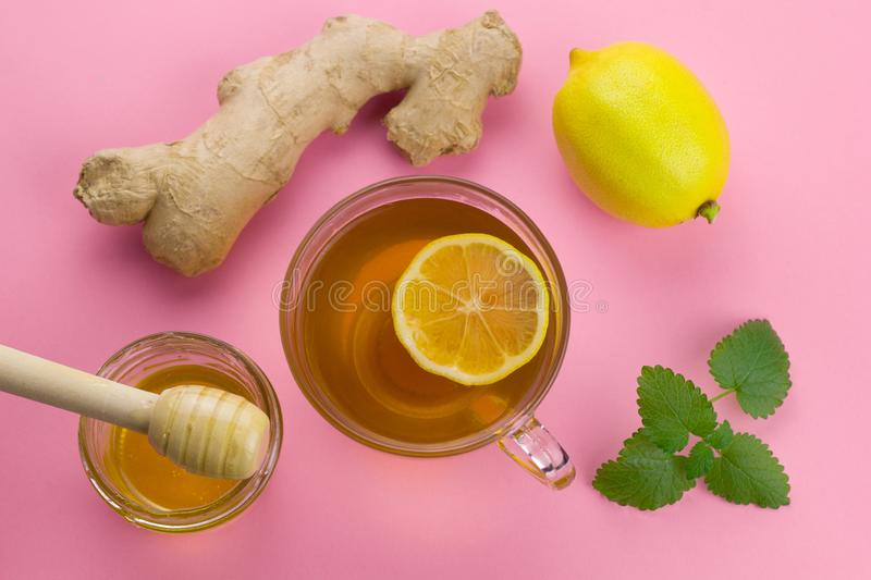 View tea, lemon,ginger, mint and liquid honey jar with wooden spoon. Top view tea, lemon,ginger, mint and liquid honey jar with wooden spoon on a pink vibrant stock photography