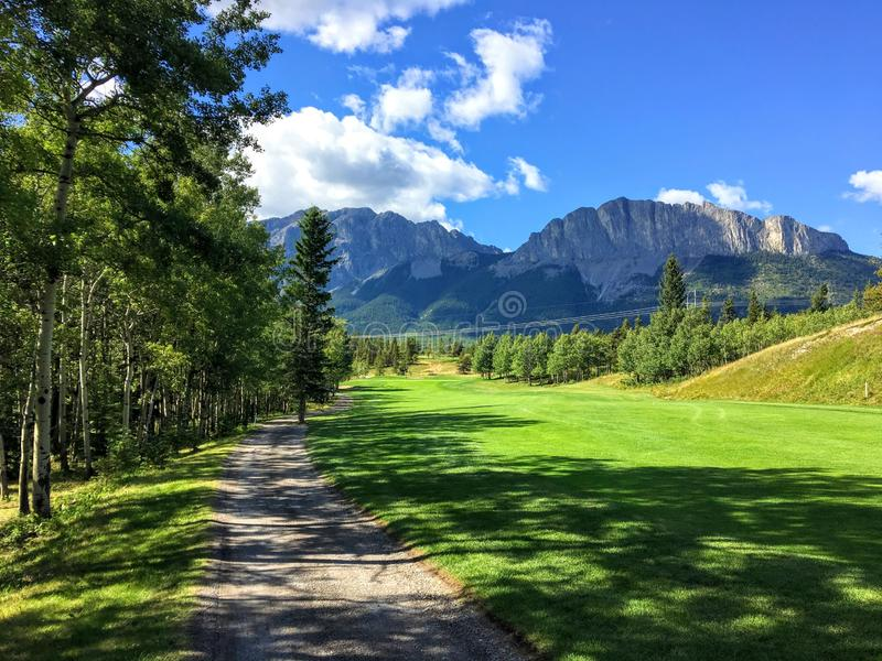 A view from the tee box looking down a tough par 4 lines with trees and the rocky mountains in the background. It is a beautiful sunny day playing golf in stock photography