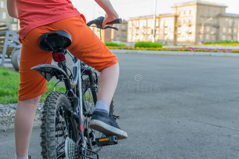 View of a teenager who sits on a bike stock photography