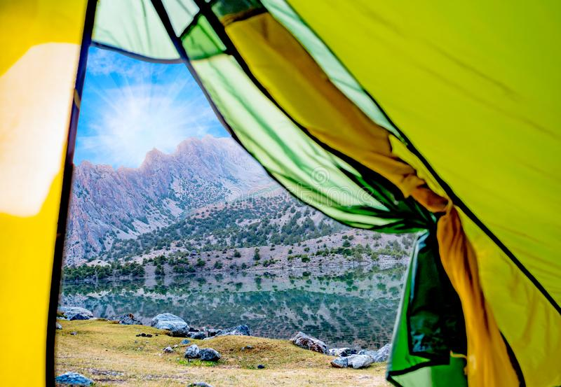 View from the tent to the Alaudin lake and rocky mountain. Fann Mountains stock images