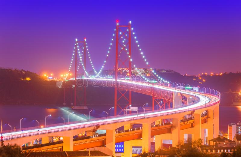 View of The 25th April Bridge Ponte 25 de Abril with car light trails in haze. Popular landmark of Lisbon, Portugal royalty free stock photography