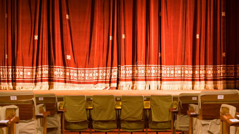 View from within a theater with stage chairs and red curtain stock photography