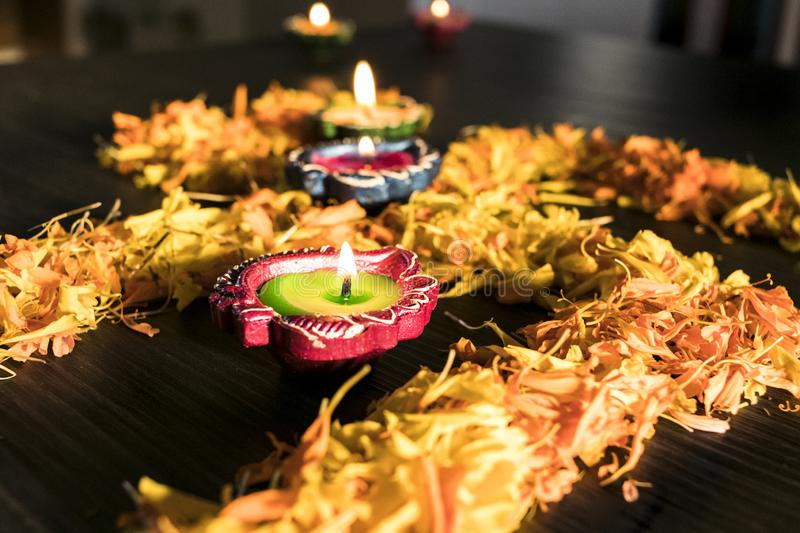 Dhanteras and diwali background.diwali greetings and wishes. A view of three illuminated diya placed on swastik to celebrate dhanteras and diwali festival royalty free stock image