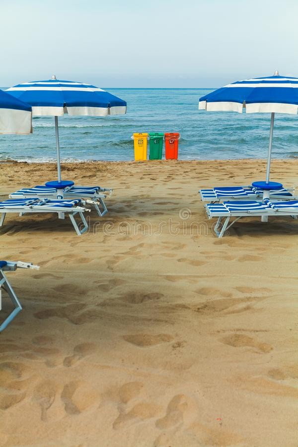 A view of three trash bin in yellow, green and red colours on a beach with some beach umbrellas stock photography