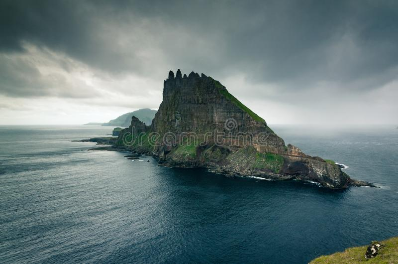 View at the Tindholmur islet with its high steep vertical wall, Mykines island in the background, Faroe Islands royalty free stock image
