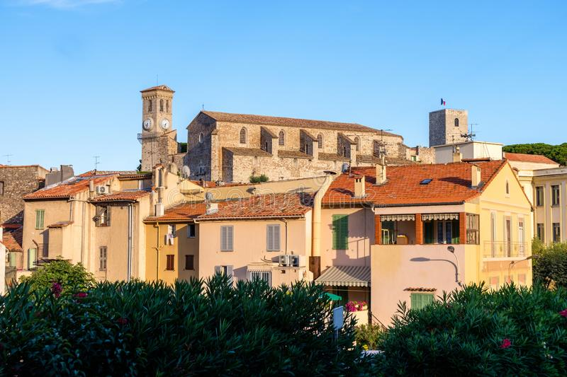 View to an ancient clock tower of a church in Cannes. Houses nearby. Old French architecture. Populated zone stock photo
