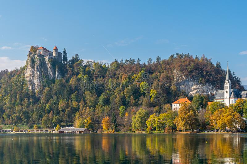 View to lake and castle on top of hill. View to beautiful lake Bled surrounded by trees and famous red roof castle on peak of hill on clear day. Travel royalty free stock photo