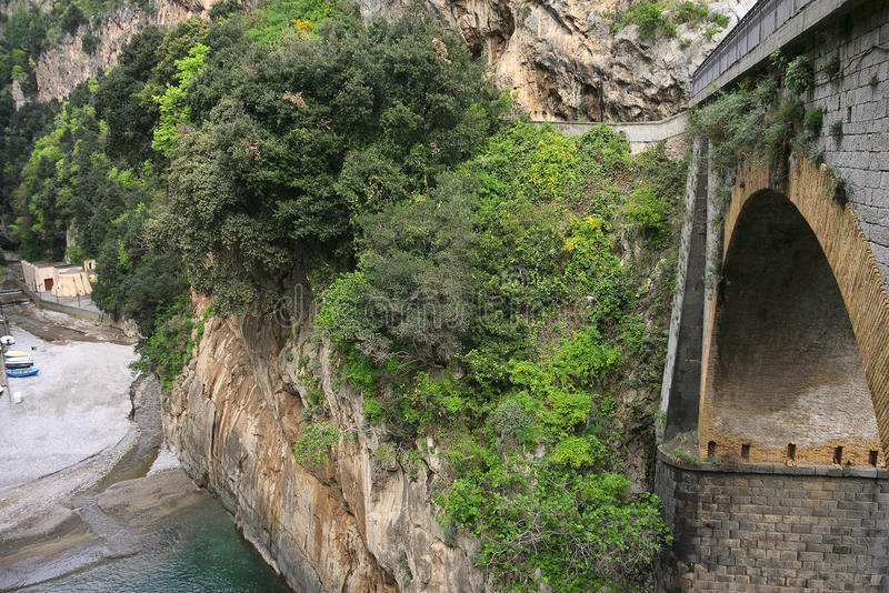 View to the bridge and beach hidden among rocks covered with green trees stock photo
