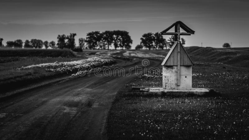 A view to a draw well in a field with flowers stock photo