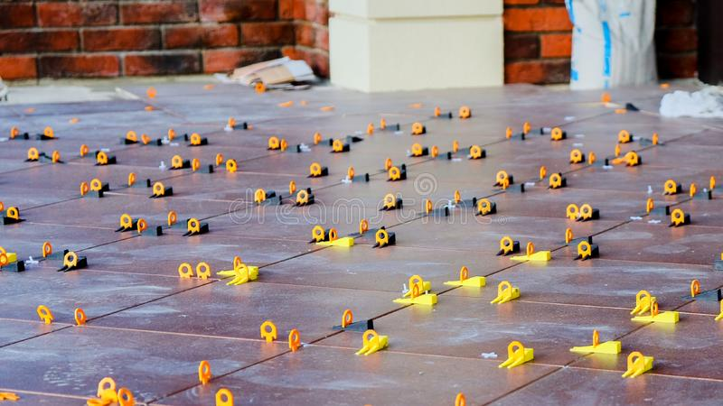 View to flooring surface with just installed new ceramic stoneware tiles with unusual creative yellow leveling spacers close up royalty free stock photos