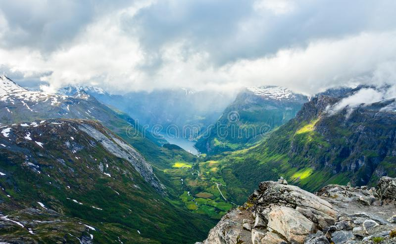 View to the Geiranger fjord with green valley surrounded by mountains, Geiranger, Sunnmore region, More og Romsdal county, Norway. Norwegian, bay, cap, country stock images