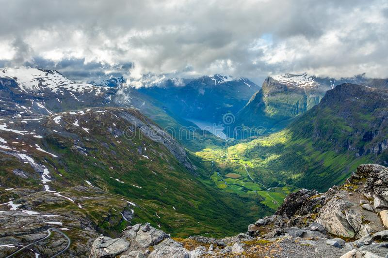 View to the Geiranger fjord with green valley surrounded by mountains, Geiranger, Sunnmore region, More og Romsdal county, Norway. Norwegian, bay, cap, clouds stock photo