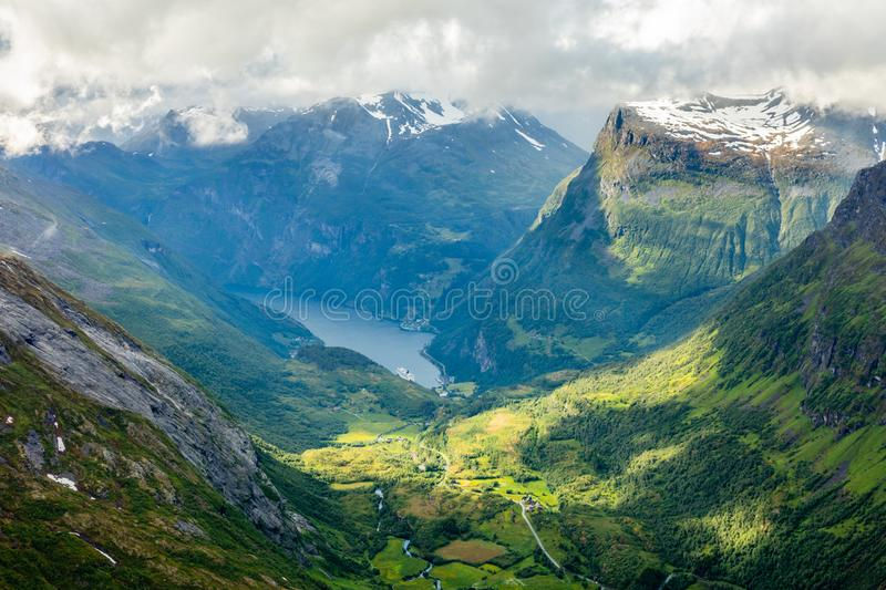 View to the Geiranger fjord with green valley surrounded by mountains, Geiranger, Sunnmore region, More og Romsdal county, Norway. Norwegian, bay, cap, clouds stock image