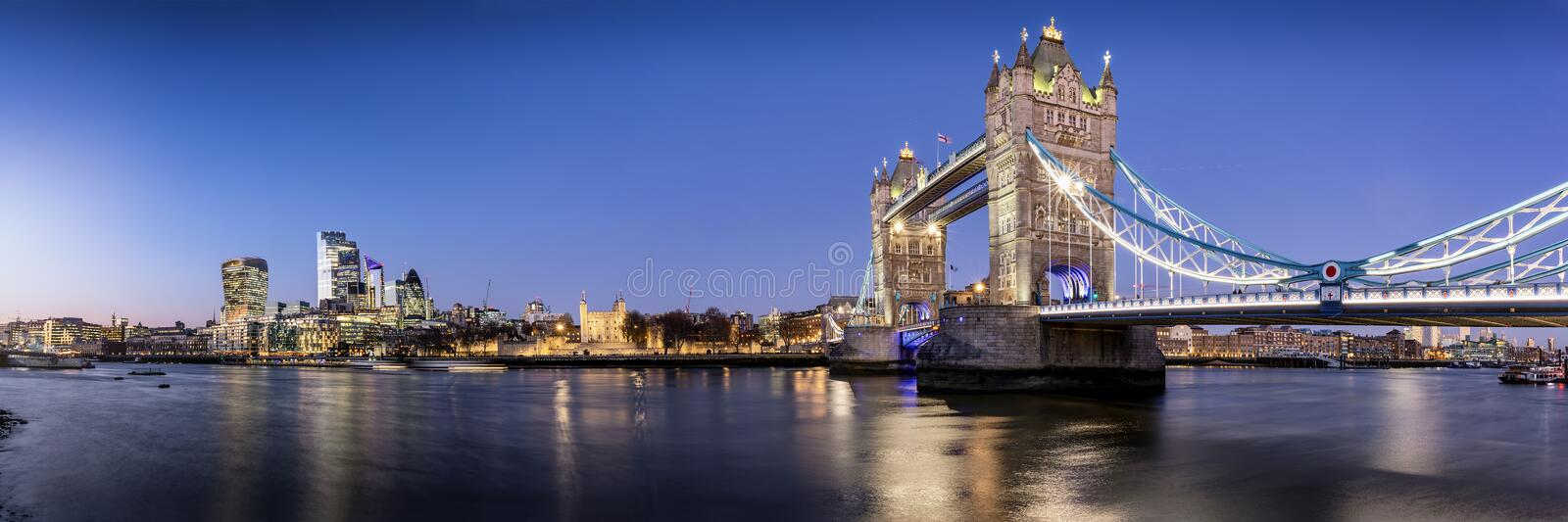 View to the lit skyline of London, UK, during evening: from the Tower Bridge along the river Thames. To the modern office skyscrapers of the city district stock photo