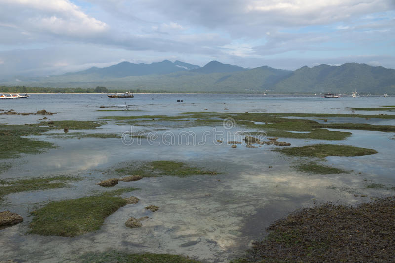 VIew to Lombok mountains from the beach of Gili Air during sunset, Indonesia. VIew to Lombok mountains from the beach during low tide of Gili Air during sunset royalty free stock images