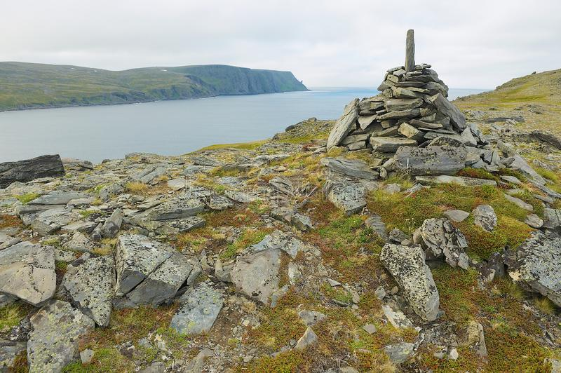 View to the Mageroya Cape and sea with the stack of stones at the fore ground in North Cape, norway. royalty free stock photography