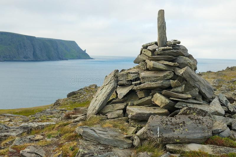 View to the Mageroya Cape and sea with the stack of stones at the fore ground in North Cape, norway. royalty free stock photo