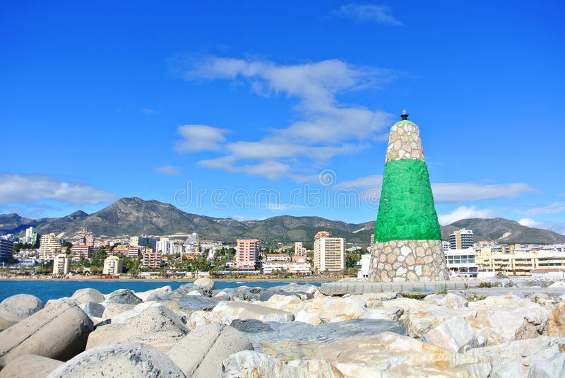 A view to Mediterranean sea, a lighthouse with breakwaters and hotels at the background from a pier at Benalmadena stock photo