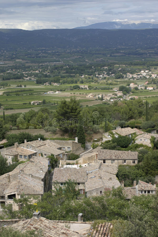 View to Mont Ventoux from Bonnieux in the Luberon. France. View to Mont Ventoux from Bonnieux in the Luberon. Village rooftops and valley stretching towards Mont stock image