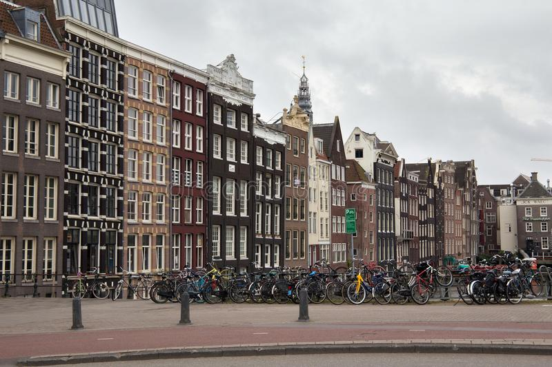 AMSTERDAM, NETHERLANDS - JUNE 25, 2017: View to the old historical dutch buildings in Amsterdam. View to the old historical dutch buildings and bicycles parking stock photos
