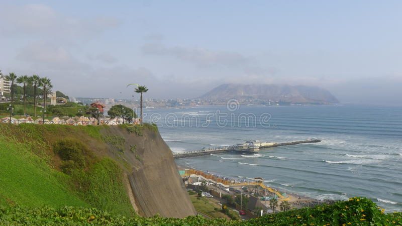 View to a park and the coastline of Miraflores. Scenic view to Parque del Amor (Love park) in Miraflores district of Lima. Also, the cliff, a pier, the Pacific stock photography