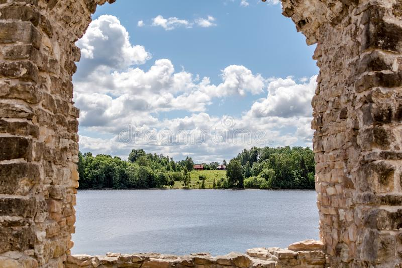 View to the rural cottage at river bank through ruins of Koknese Castle stock photography