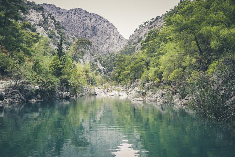 View to small beautiful lake surrounded by forests and mountains. stock image