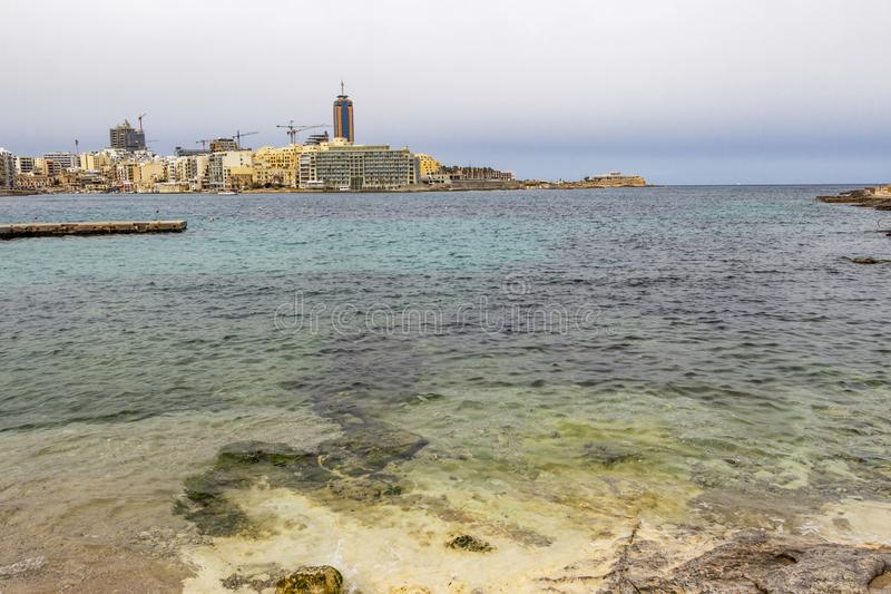 View to St. Julian`s with part of the limestone shore at St. Julian`s Bay, Malta stock images