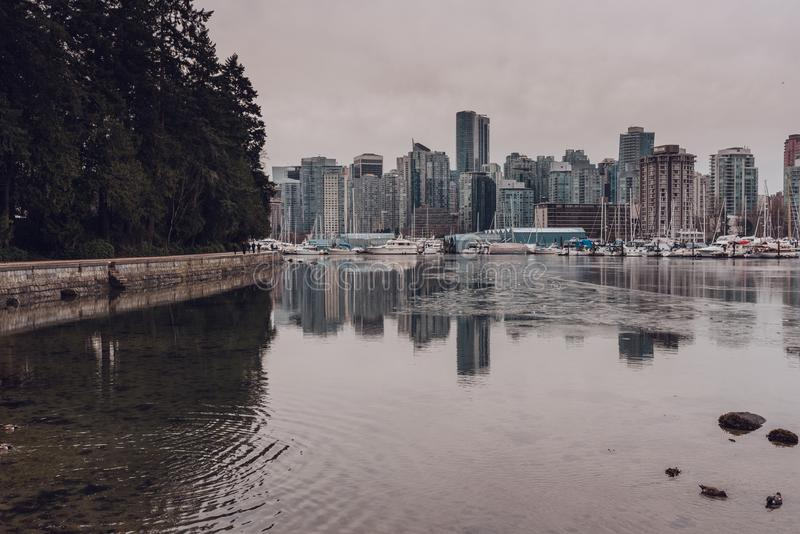 View to Stanley park seawall, skyscrapers and harbour reflexting in the water on overcast winter day. Vancouver, British Columbia stock images