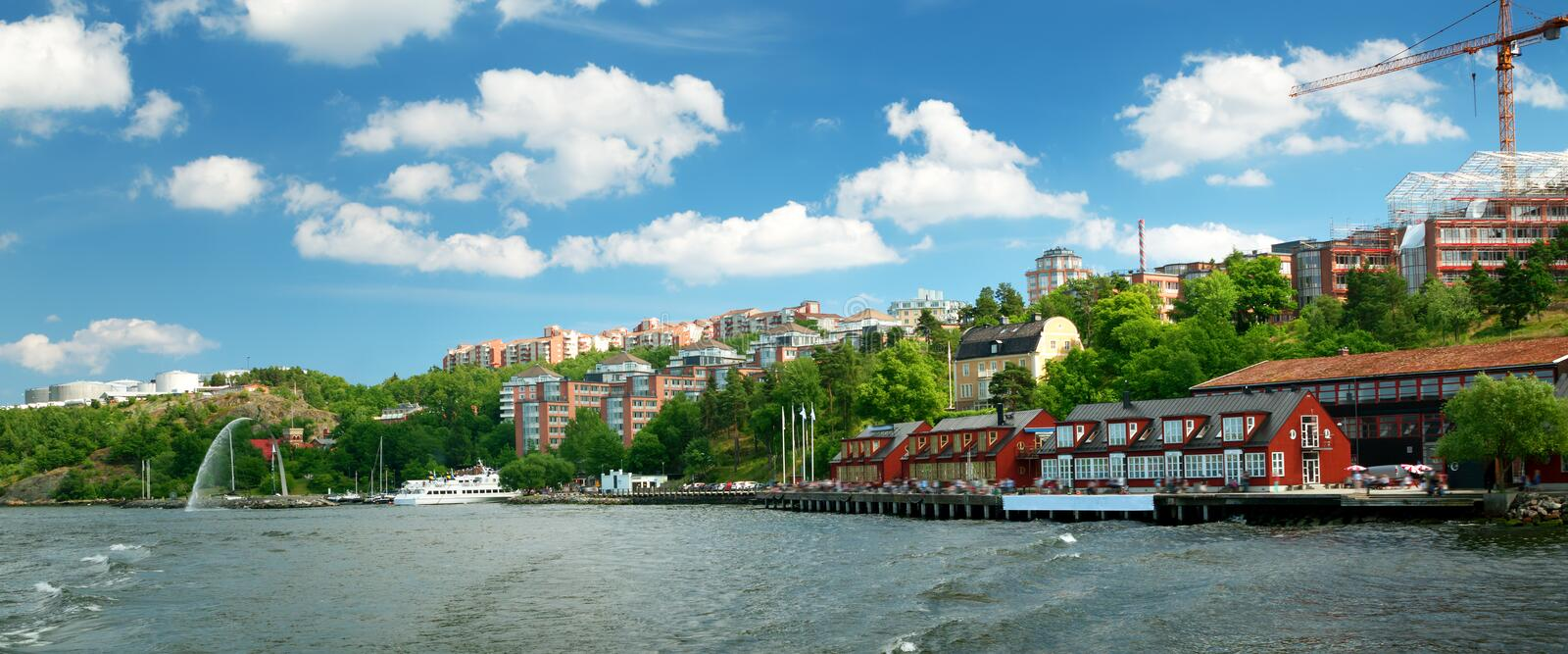 View to Stockholm with a small pier near Nacka strandt. View to Stockholm, Sweden with a ferry from sea in summer. Nacka strand houses and harbour on sunny day stock image