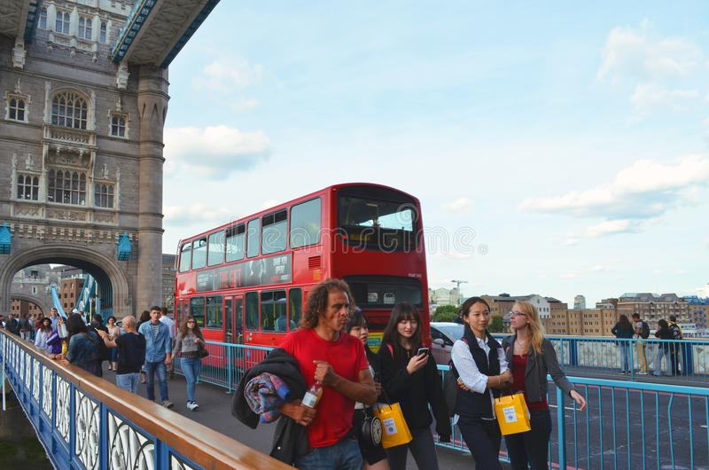 View to a typical red London bus and pedestrians on the walkway of the Tower Bridge royalty free stock images