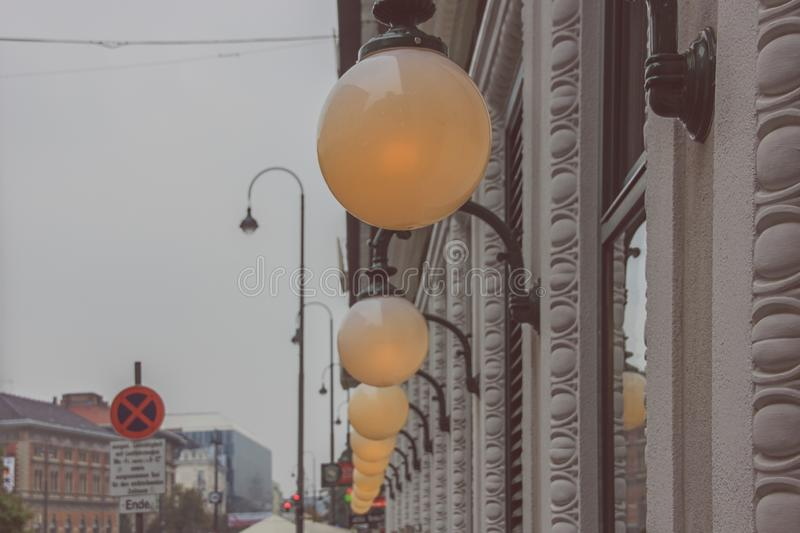 View to wall of old gray-pink building with carved decorative facade elements and switched white glass ball lamps in row  due stro. Ng mist and rain in city stock images