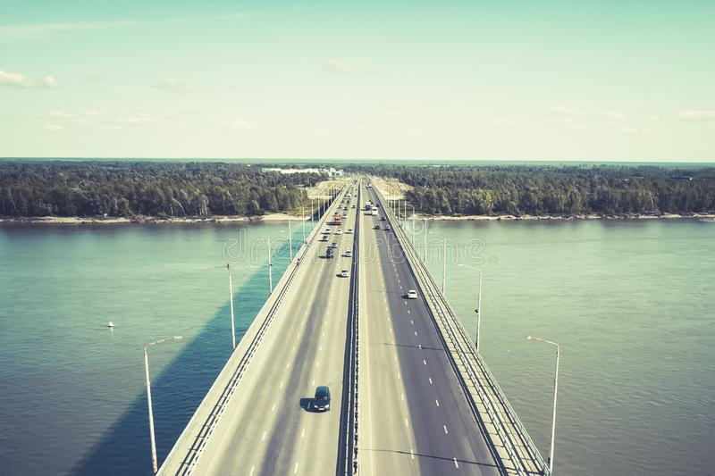 A view to the well-consrtucted city bridge across the river. City river gates. Cars on the bridge moving in and out of the city at royalty free stock photos