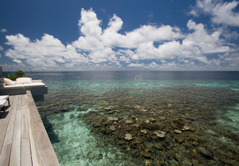 View to the wooden deck and ocean. View from the private wooden deck of the tropical villa to the calming deep blue ocean. Corals are visible because of royalty free stock photography