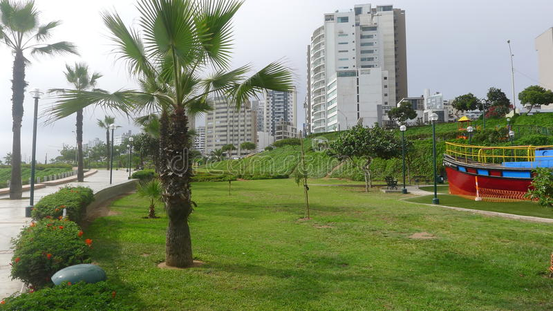 View to Yitzhak Rabin park in Miraflores, Lima. Scenic view to Yitzhak Rabin park in Miraflores district of Lima with lawn, palms, exterior buildings a royalty free stock photo
