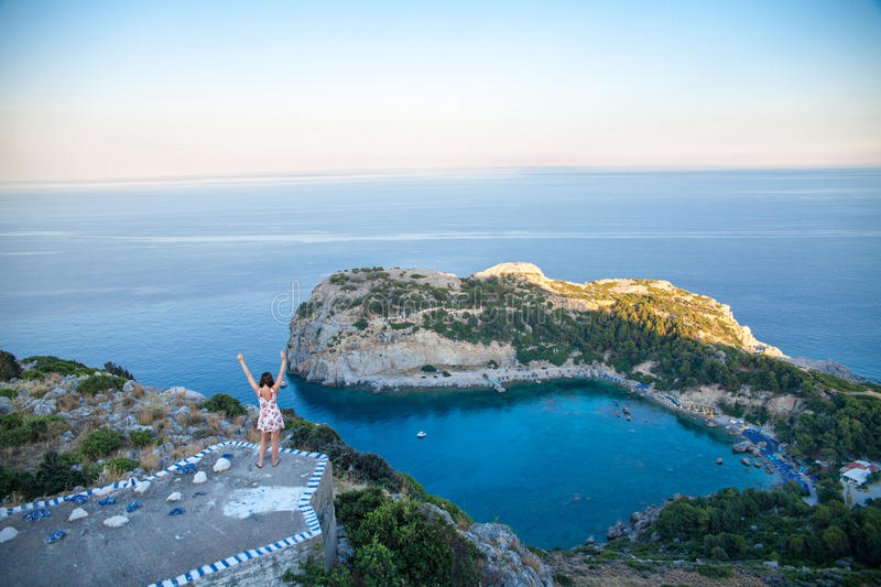 View from top on Anthony Quinn Bay and beach, Rhodes in Faliraki, Greece. Happy girl Raising One Hand. Beautiful beach and bay on royalty free stock photo