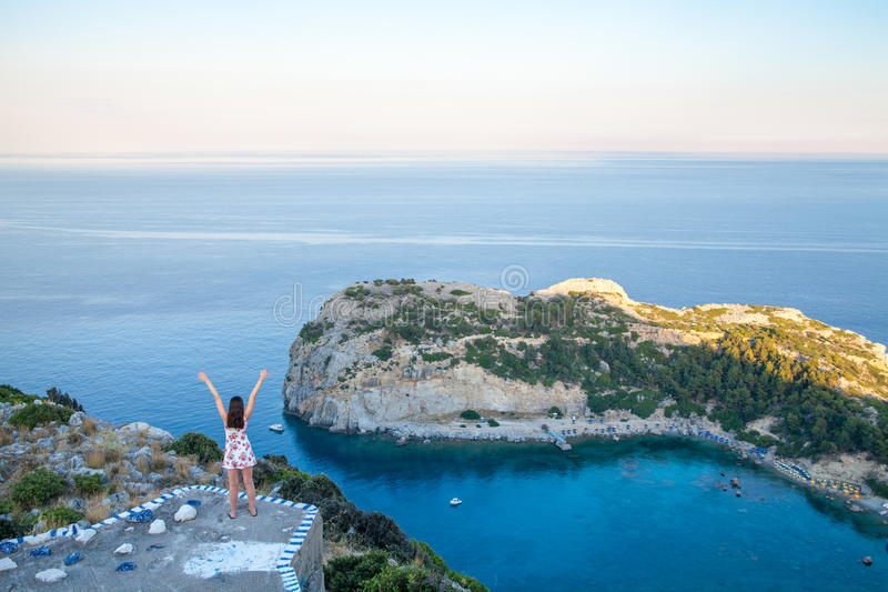 View from top on Anthony Quinn Bay and beach, Rhodes in Faliraki, Greece. Happy girl Raising One Hand. Beautiful beach and bay on. The island of Rhodes royalty free stock photography