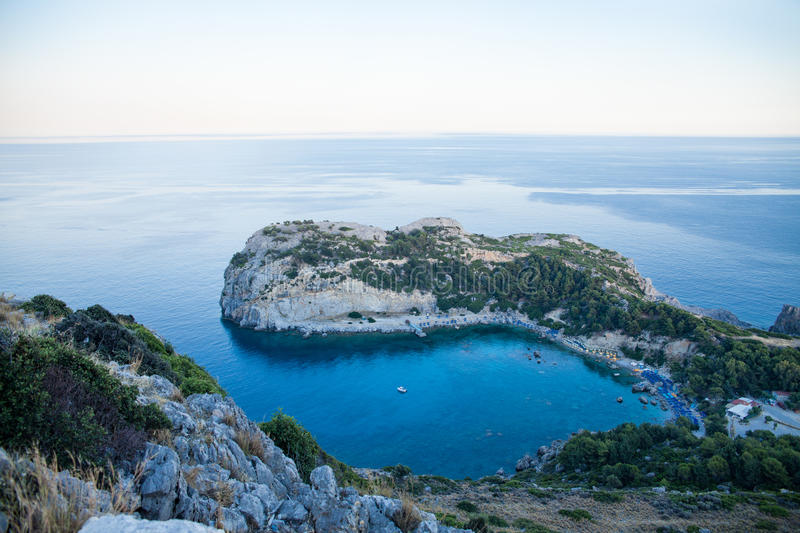 View from top on Anthony Quinn Bay and beach, Rhodes in Faliraki, Greece. Happy girl Raising One Hand. Beautiful beach and bay on royalty free stock images