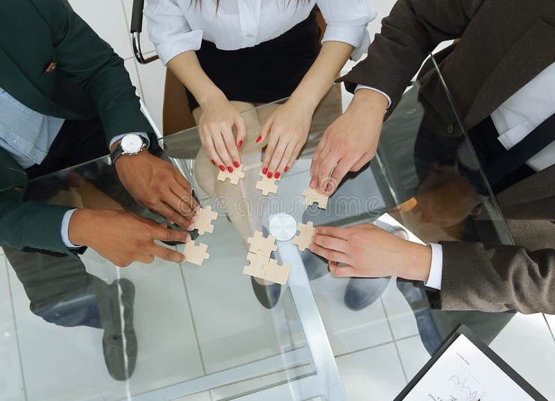 View from the top.business team folding puzzle pieces. royalty free stock photography