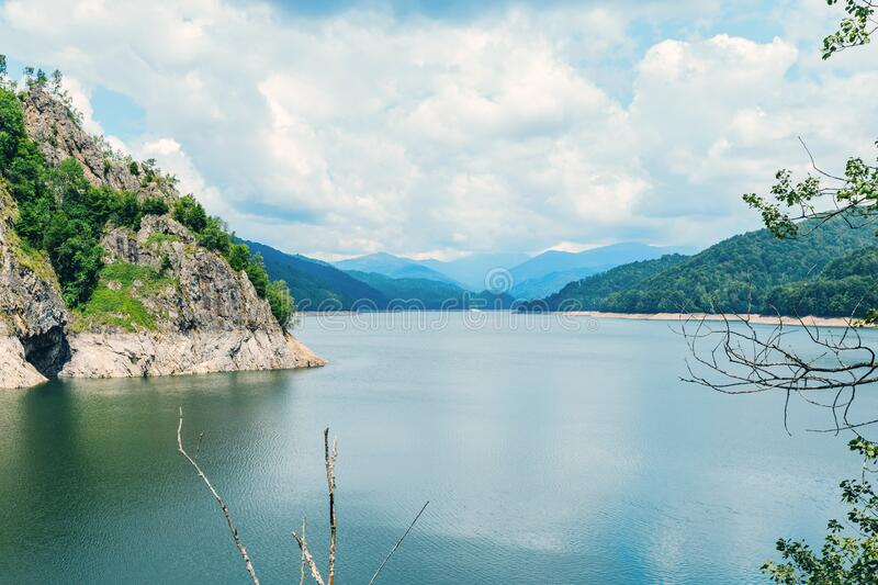 View from the top of the dam Vidraru to the landscape of mountains and lake Vidraru, Romania stock photography