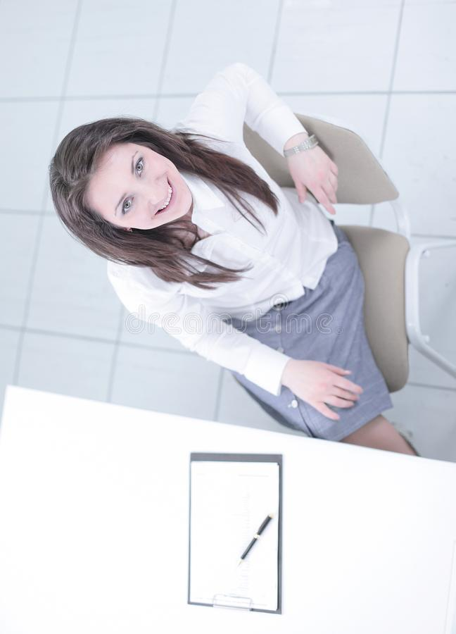 View from the top.employee sitting at Desk and looking at camera. Photo with copy space stock images