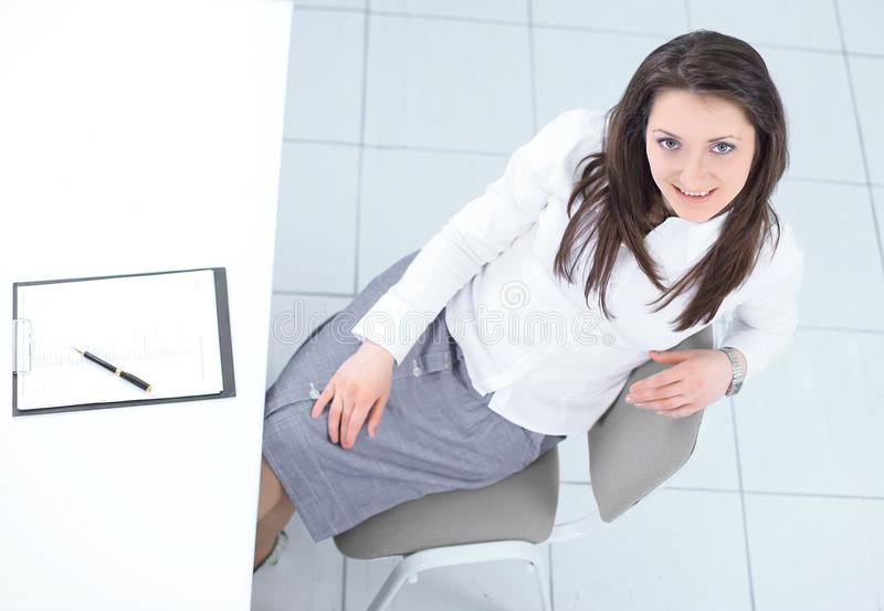 View from the top.employee sitting at Desk and looking at camera. Photo with copy space royalty free stock photography