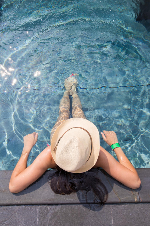View from the top of a girl relaxing in the swimming pool. View from the top of a girl in a hat relaxing in the swimming pool royalty free stock photo